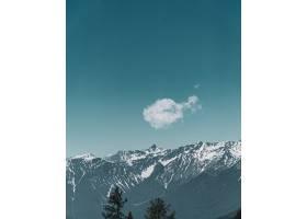 以山和蓝天为背景的可爱小云的垂直视图_1060600301