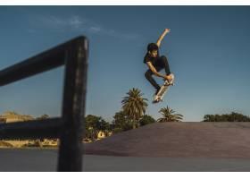 低角度拍摄一名男子在空荡荡的滑板公园玩滑_1086086401