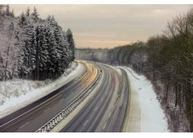 冬天白雪覆盖的森林中有树木的道路这是_1204545201
