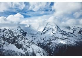 冬季多云天空下白雪皑皑的高山戏剧性全景_1127804901