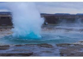 冰岛多云天空下群山环绕的Strokkur间歇泉_985219501