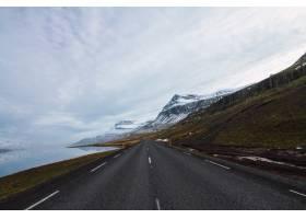 冰岛多云天空下被河流和覆盖着雪和草的小山_997058801