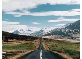 冰岛多云天空下被绿色和积雪覆盖的山丘包围_1011958201