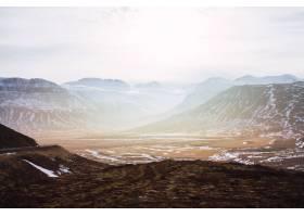 冰岛多云的天空和阳光下覆盖着草和雪的山丘_1018617201