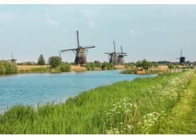 前景为绿草的传统荷兰风车荷兰_948023501