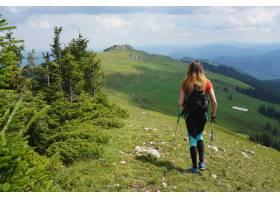 一位女徒步旅行者在夏天蓝天下在山上徒步旅_1099086501