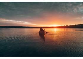 一名女子在日落时在湖中央划着皮划艇的美丽_802422601