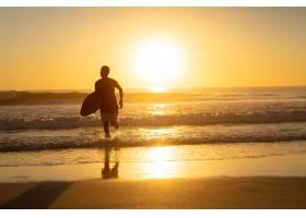 一名男子在海滩上带着冲浪板跑步_519537401
