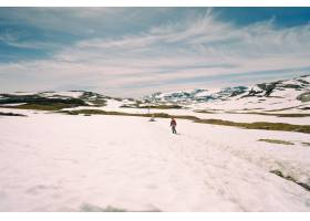 一名男子在雪山上行走的低角度拍摄_1306181001