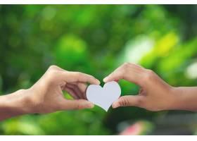 一对情侣在绿色的草地上手牵手_1039960201