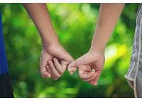 一对情侣在绿色的草地上手牵手_1039960401