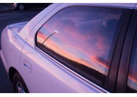 一辆紫色轿车的车窗上映出的夕阳的美丽色彩_1039923701