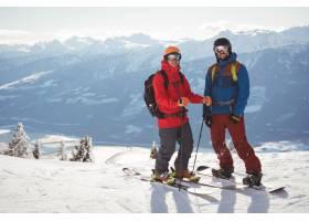 两个滑雪者一起站在积雪覆盖的山上_1123049801