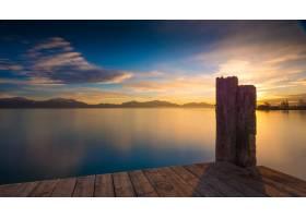 风平浪静的海面上有山脉和日出的木制码头_9655401