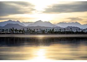 风景的天空在落日的灯光下倒映在海面上城_11915034