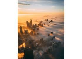 高角拍摄了日落时白云覆盖的城市景观和高耸_11342932