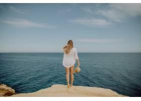 美丽的晒黑的女人抬起手看着大海_10370906