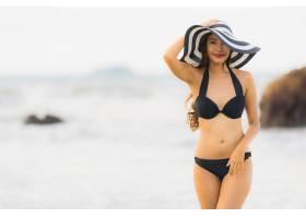肖像美丽的亚洲年轻女子在海滩海边穿着比基_5017299