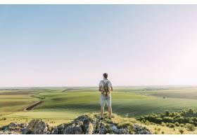 背着背包看着绿色起伏的风景的男性徒步旅行_2593196