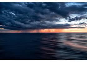 落日天空中的乌云笼罩在黑暗的海洋水面上_9852498