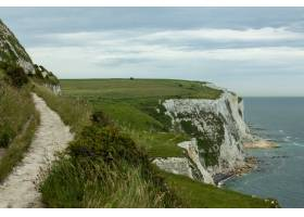 英国多云天空下绿树成荫的多佛白色悬崖_12040360