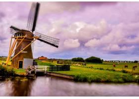 荷兰多云天空下湖边风车的美丽镜头_10835681