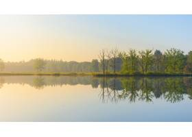 蓝天下宽阔的水面映照着岸上的绿叶树木_8280983