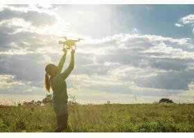 田野里的一名年轻女子将无人机发射上天_10507538