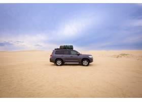 白天在多云的天空下的沙漠里一辆载着行_9852391