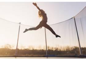 活跃的小女孩在天空的衬托下跳过蹦床_2728229