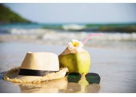 海浪沙滩上戴着帽子和太阳镜的新鲜椰子带_5073597