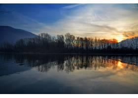 湖面上美丽的日落景色水中倒映着树木的剪_10979133