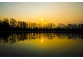 湖面上美丽的日落景色水中倒映着树木的剪_11111324