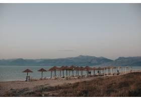 海滩的美丽景色草沙滩伞下有躺椅_13234983