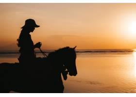 海边金灿灿的夕阳中年轻女子在海滩上骑马_8270054