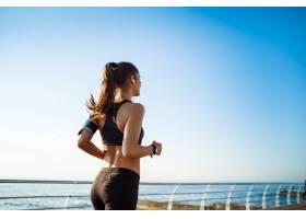 年轻迷人的健身女子与大海在墙上慢跑的照片_9320743