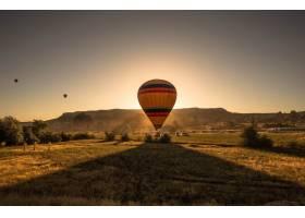 日落时分一只五颜六色的热气球在绿树成荫_11526540