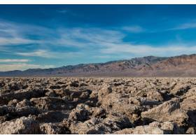 沙漠中的岩石地面和背景中明亮的蓝天的美丽_8281059
