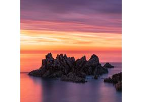 日落时分根西岛五颜六色的天空下海堆的_10376902