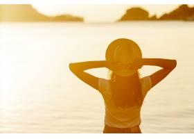 日落时分湖边戴着帽子的女人_5903517