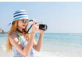 快乐的亚洲女人度假在海滩上用相机拍照_1371520