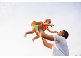快乐的父亲在夏日的天空下抱着迷人的小女孩_2437863