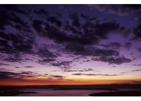 日落时海面上有云的紫色天空的美丽镜头_7814495