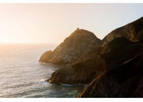 日落时蓝天下平静的海洋和岸上悬崖的迷人景_11890906