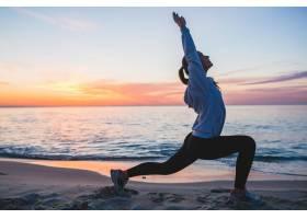 早晨一名年轻女子在日出海滩上进行体育锻_9629466