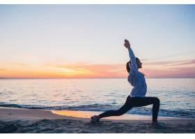 早晨一名年轻女子在日出海滩上进行体育锻_9629469