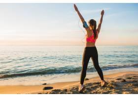 早晨一名年轻女子在日出海滩上进行体育锻_9629530
