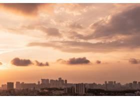 晚间日落时多云天空下的城市景观_10584460