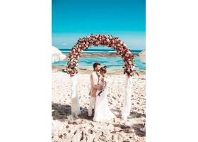 新娘和新郎在蓝天和大海背后的海滩上摆着接_6883636