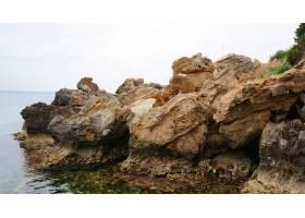 拥有大海和蓝天的岩石海滩的美丽景色_9931736